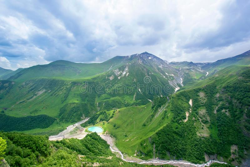 Belles crêtes de montagnes énormes dans la neige, ciel bleu, nuages blancs, lac bleu au pied de la montagne, collines vertes, val photo libre de droits