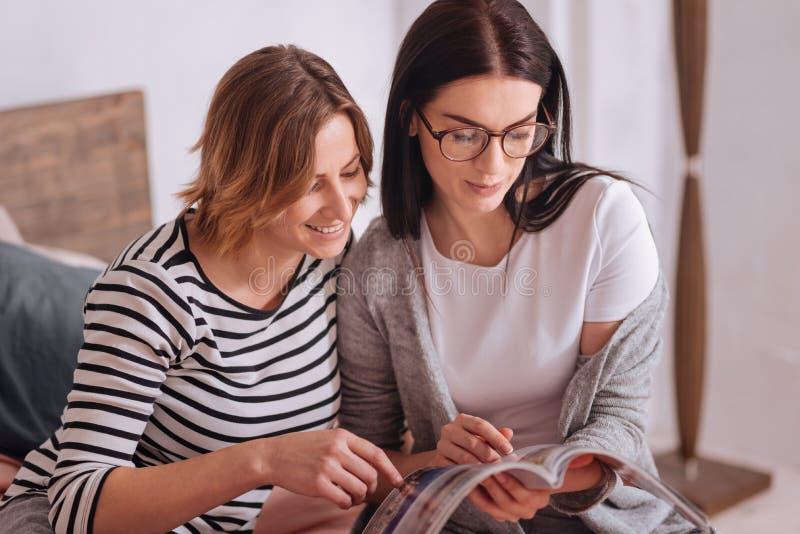 Belles dames intéressées regardant par un article image stock