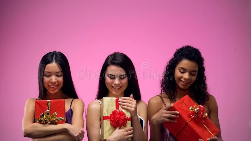 Belles dames regardant des giftboxes dans des mains, le meilleur pr?sent pour l'ami, vacances photos stock