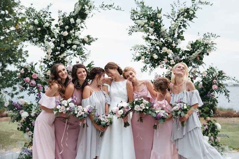 Belles demoiselles d'honneur de sourire minces élégantes dans la robe beige rose sensible d'été sur la cérémonie l'épousant images stock