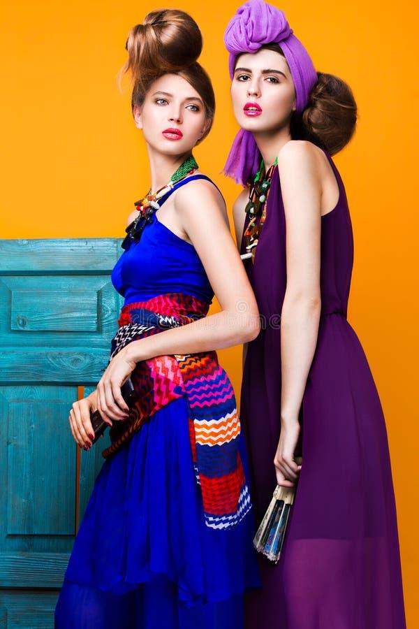 Belles femmes à la mode une coiffure peu commune dans les vêtements lumineux et des accessoires colorés Style cubain photographie stock libre de droits