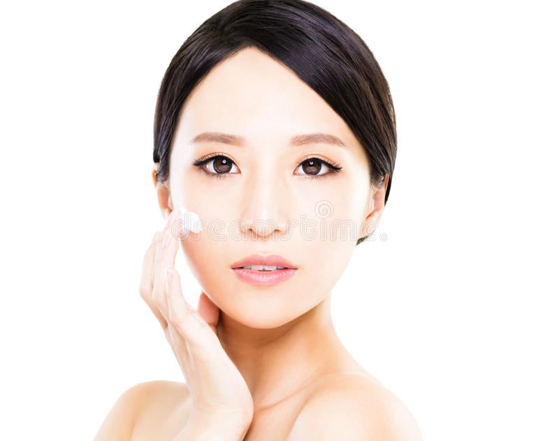 Belles femmes appliquant la crème cosmétique de crème hydratante sur le visage photographie stock