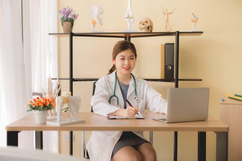 Belles femmes asiatiques de docteur s'asseyant et travaillant au bureau utilisant l'ordinateur portable et écrivant la note à l'h photographie stock