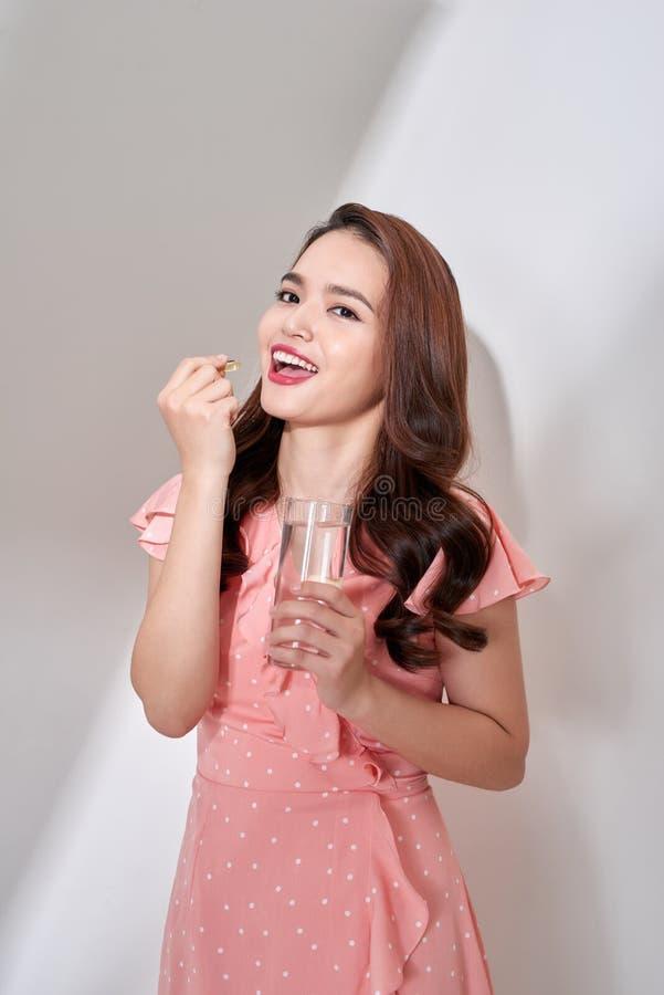 Belles femmes asiatiques mangeant la pilule de vitamine pour des soins de santé à la maison photographie stock