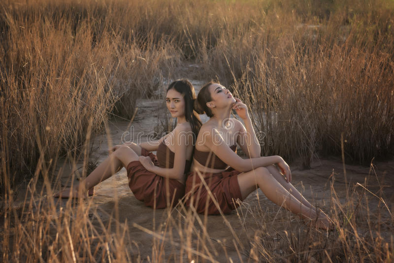 Belles femmes asiatiques s'asseyant dans le domaine d'herbe portant la tradition thaïlandaise photo libre de droits