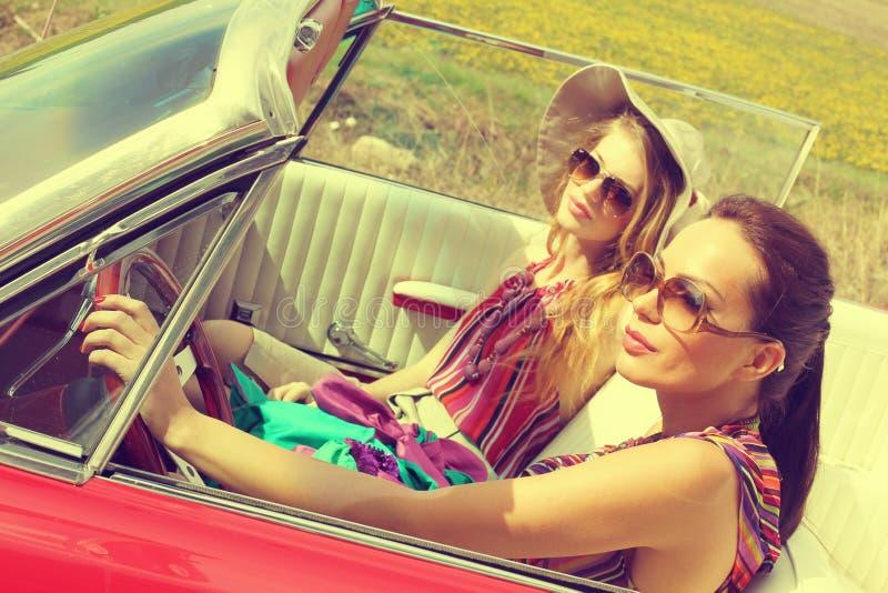 Belles femmes conduisant les accesoriess de port vintage rouge de voiture d'un rétro photos stock