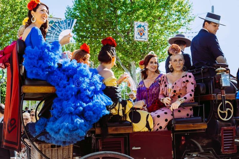 Belles femmes dans la robe traditionnelle et colorée voyageant dans chariots hippomobiles chez April Fair, foire de Séville image libre de droits