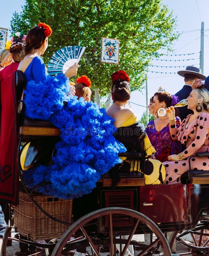 Belles femmes dans la robe traditionnelle et colorée voyageant dans chariots hippomobiles chez April Fair, foire de Séville photos libres de droits