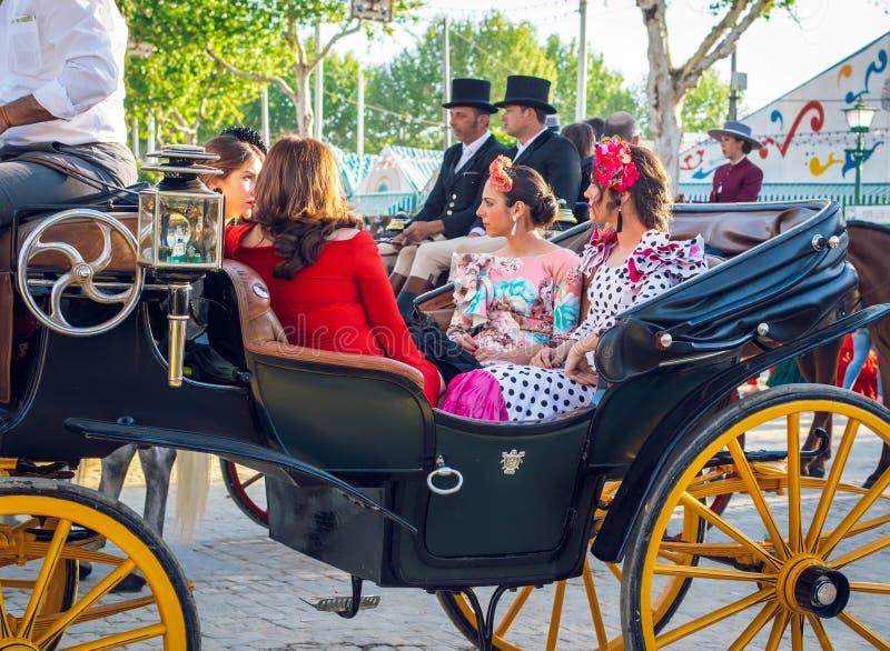 Belles femmes dans la robe traditionnelle et colorée voyageant dans chariots hippomobiles chez April Fair, foire de Séville images stock