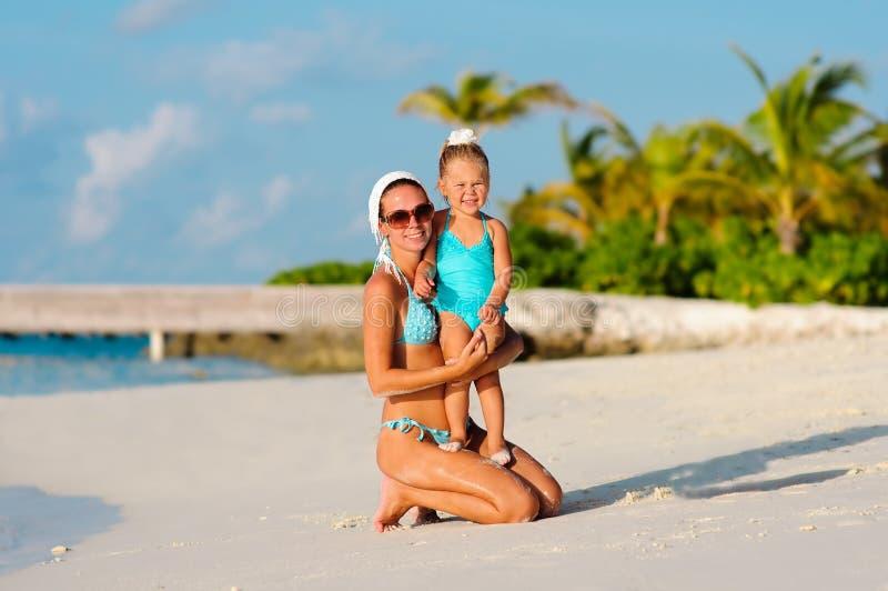 Belles femmes et son descendant sur la plage photo libre de droits
