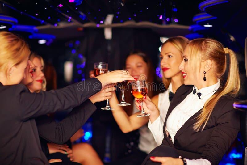 Belles femmes faisant tinter des verres dans la limousine photographie stock