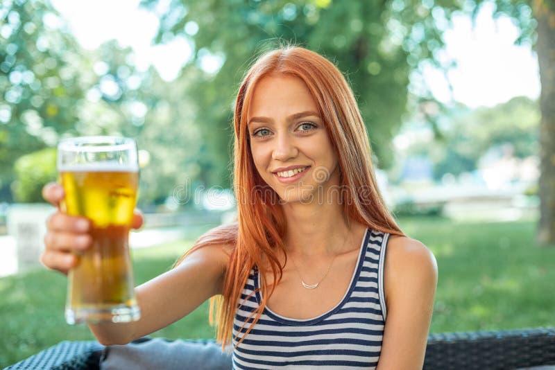Belles femmes mignonnes de Rouge-cheveux buvant de la bière image libre de droits