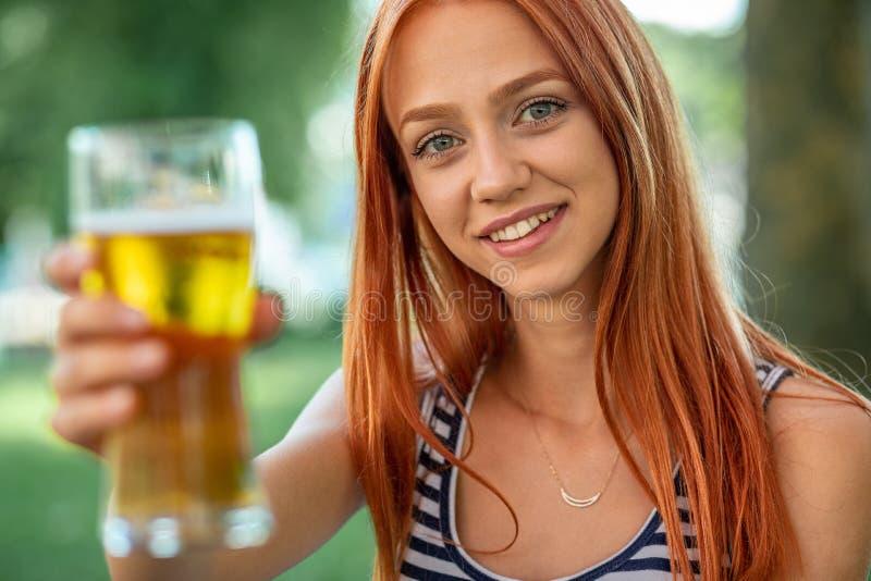Belles femmes mignonnes de Rouge-cheveux buvant de la bière images stock