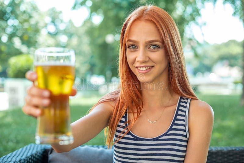 Belles femmes mignonnes de Rouge-cheveux buvant de la bière photographie stock
