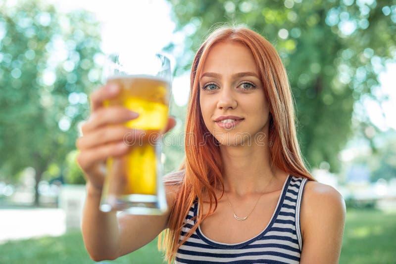 Belles femmes mignonnes de Rouge-cheveux buvant de la bière photo stock