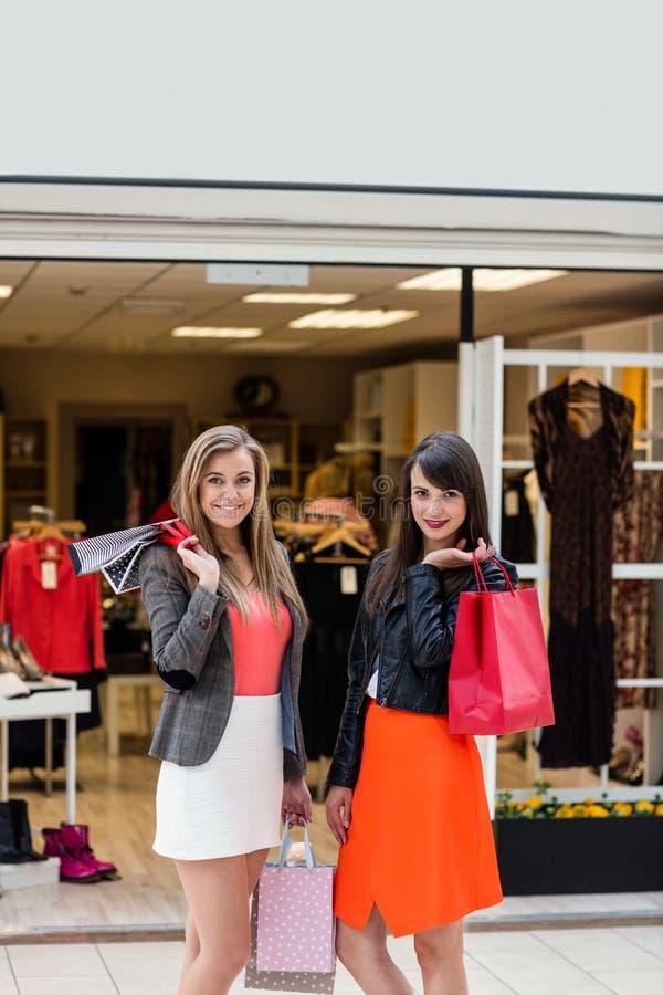 Belles femmes se tenant devant la boutique de vêtement photo stock