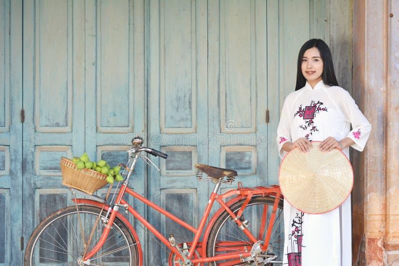Belles femmes Vietnam avec la robe blanche d'ao Dai et la bicyclette rouge dans la vieille ville photos libres de droits
