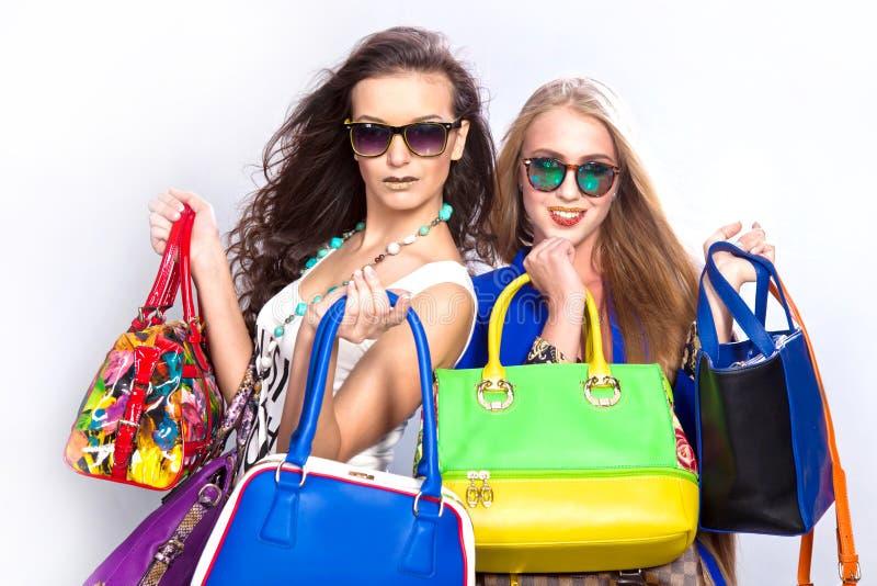 Belles filles ? la mode et beaucoup de sacs en cuir sur un fond gris photo libre de droits