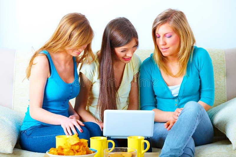 Belles filles avec l'ordinateur portatif photo stock
