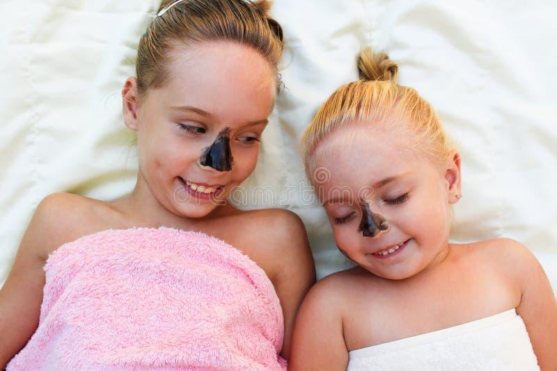 Belles filles avec le masque noir facial d'argile photographie stock