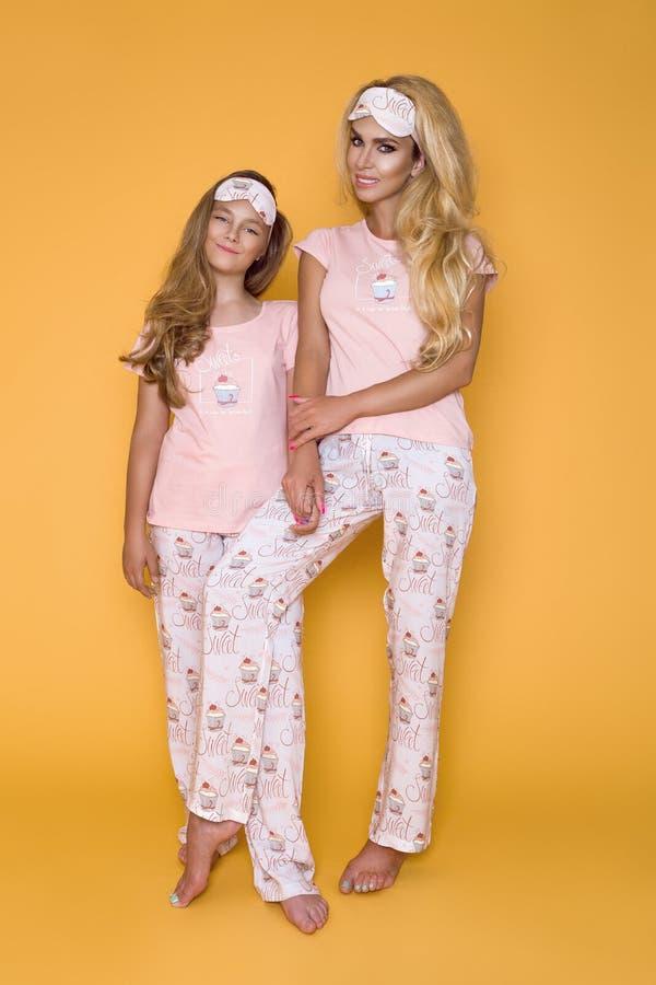 Belles filles blondes, mère avec la fille dans des pyjamas sur un fond jaune dans le studio photos libres de droits