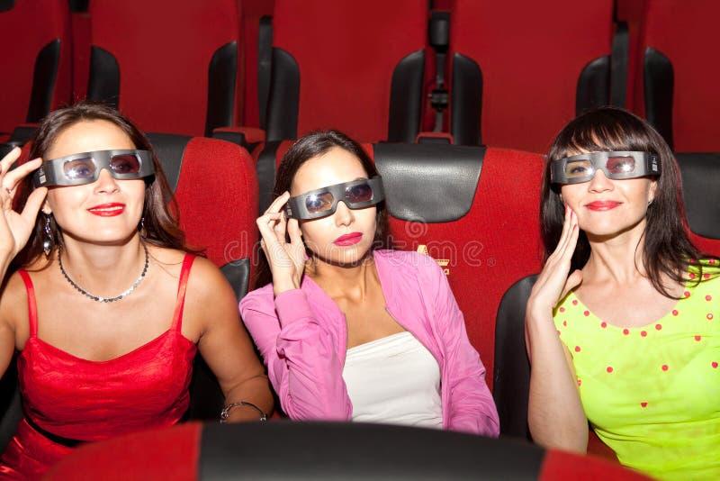 Belles filles dans un cinéma portant les lunettes 3D image libre de droits