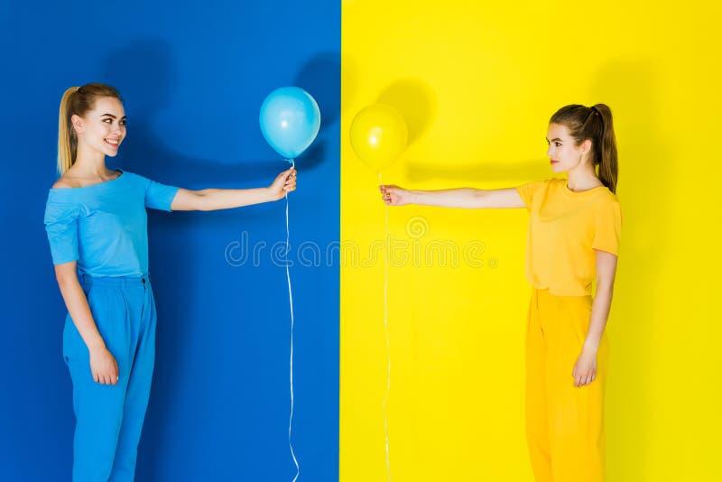 Belles filles de blonde et de brune tenant des ballons devant l'un l'autre sur le bleu images libres de droits