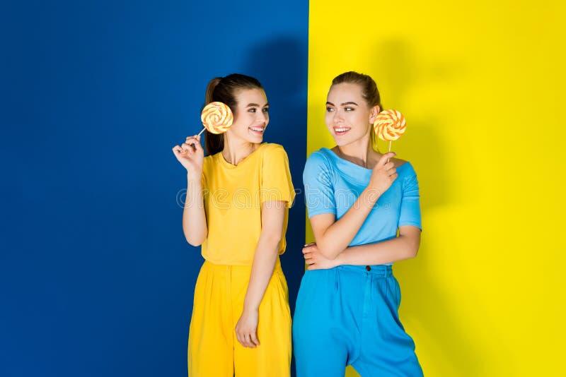 Belles filles de blonde et de brune tenant des lucettes sur le bleu photographie stock