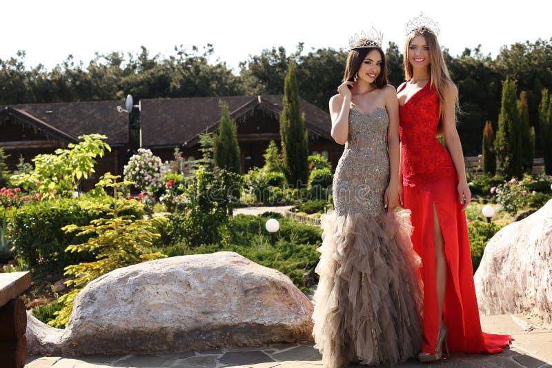 Belles filles utilisant les robes élégantes et la couronne luxueuse image libre de droits