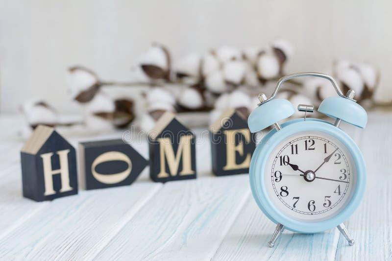 Belles fleurs blanches de coton, cubes avec des lettres et réveil bleu sur le fond en bois de turquoise photographie stock