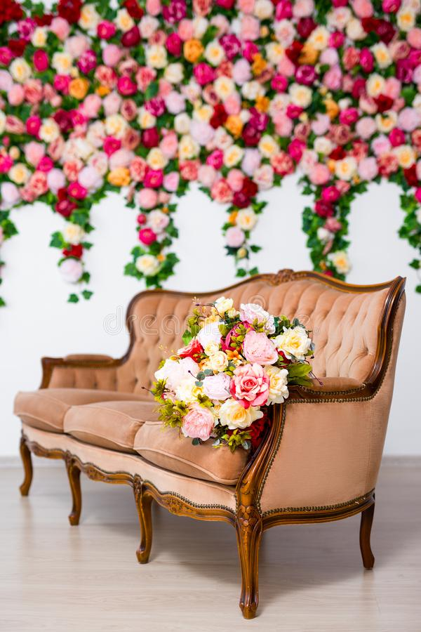 Belles fleurs sur le sofa de cru au-dessus du fond coloré de fleurs image libre de droits
