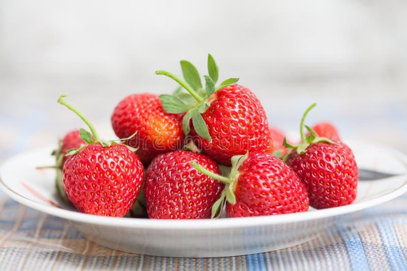 Belles fraises de plat Baies fraîches rouges avec les feuilles vertes Profondeur de la photographie de champ, macro vue photos libres de droits