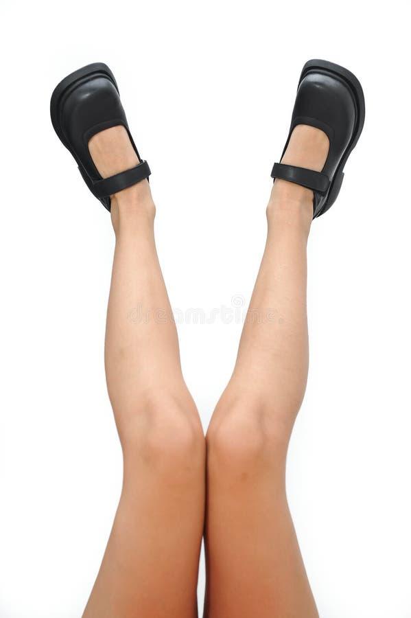 Belles jambes de femme et chaussures noires se dirigeant d'isolement sur un fond blanc photo stock
