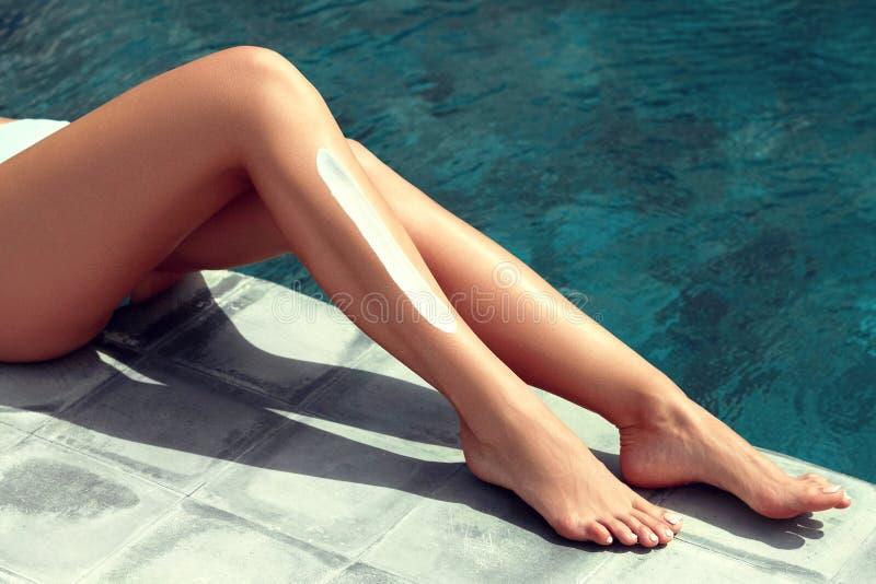 Belles jambes de femme prenant un bain de soleil pr?s de la piscine photographie stock libre de droits