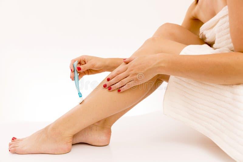 Belles jambes femelles avec l'epilator d'isolement sur le fond blanc images libres de droits
