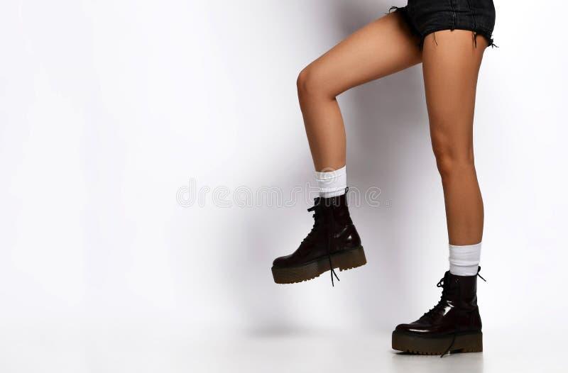 Belles jambes femelles portant les bottes noires en cuir dans des shorts de concepteurs de jeans et sauter de marche de veste ver image libre de droits