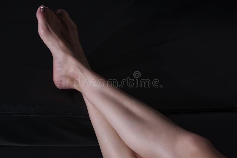 Belles jambes femelles sur le fond foncé images stock