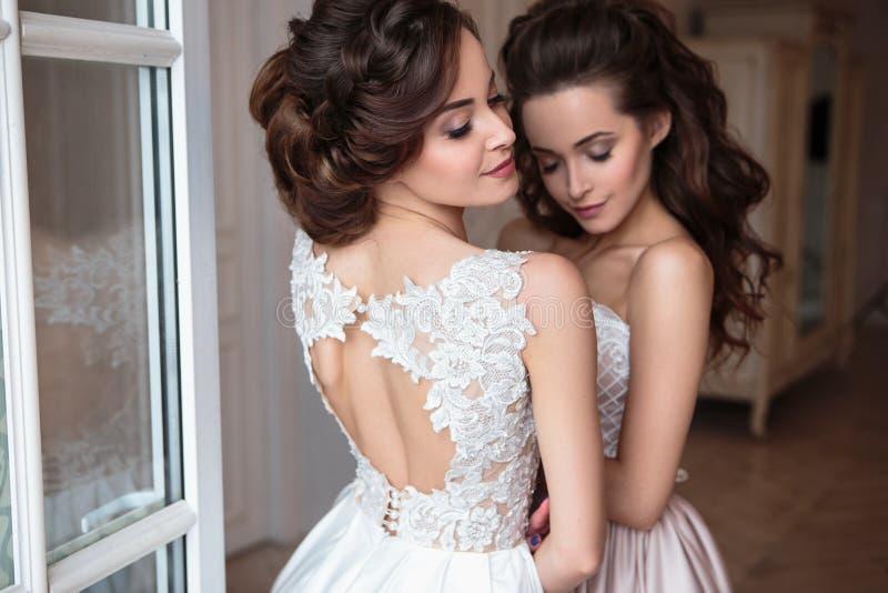 Belles jeune mariée et demoiselles d'honneur dans des robes de luxe photos stock