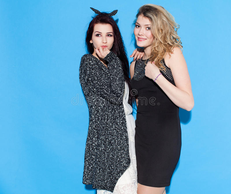 Belles jeunes amies à la mode se tenant ensemble près d'un fond bleu Avoir drôle et pose regarder l'appareil-photo Indo image stock