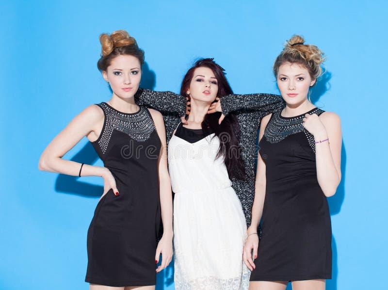 Belles jeunes amies à la mode se tenant ensemble près d'un fond bleu Deux blondes et une brune Avoir drôle et la position images libres de droits
