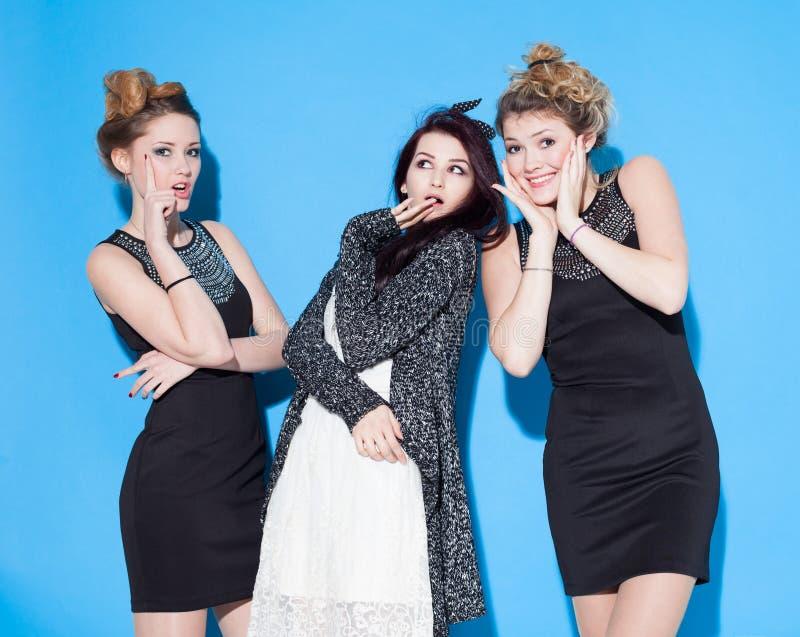 Belles jeunes amies à la mode se tenant ensemble près d'un fond bleu Deux blondes et une brune Avoir drôle et la position image libre de droits