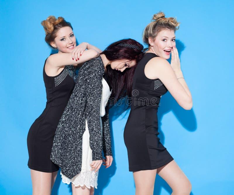 Belles jeunes amies à la mode se tenant ensemble près d'un fond bleu Deux blondes et une brune Avoir drôle et la position image stock