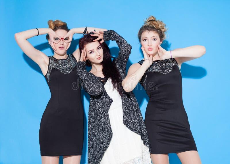Belles jeunes amies à la mode se tenant ensemble près d'un fond bleu Deux blondes et une brune Avoir drôle et la position photo libre de droits