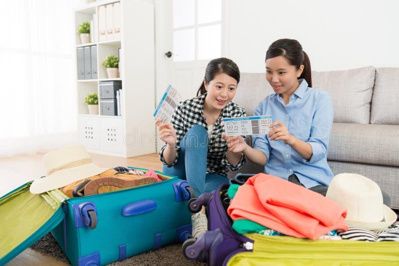 Belles jeunes amies montrant la carte d'embarquement images stock