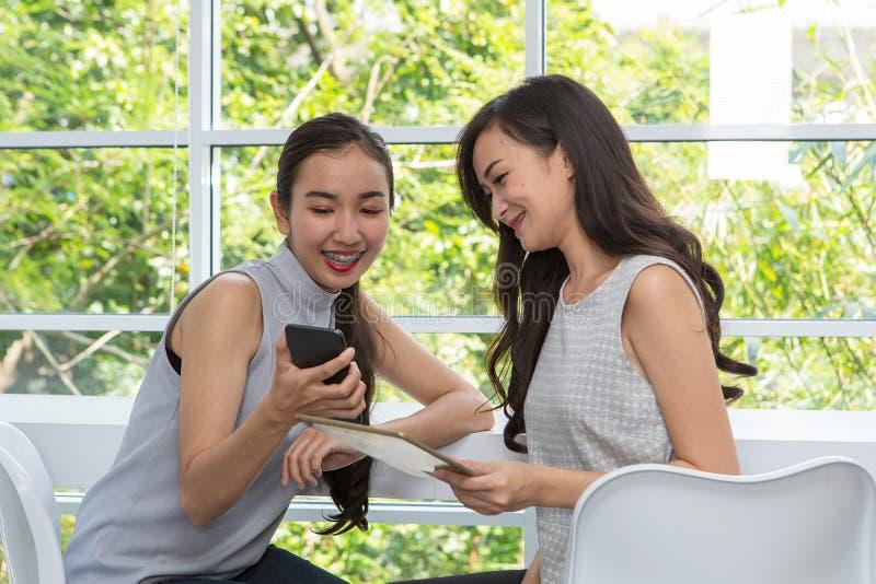Belles jeunes femmes à l'aide du téléphone portable numérique et du comprimé dans c images stock