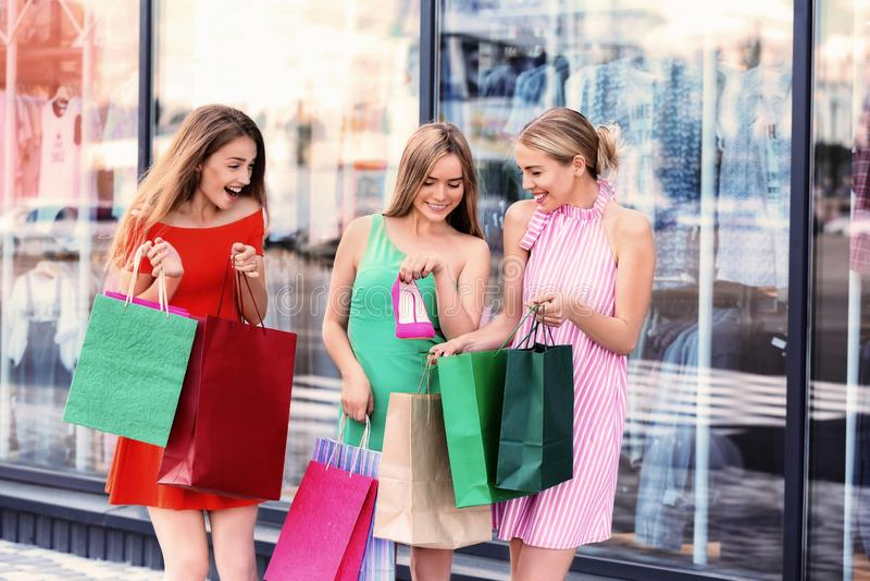 Belles jeunes femmes avec des sacs à provisions près de magasin sur la rue de ville photographie stock libre de droits
