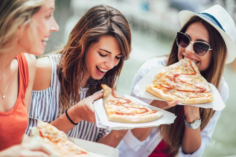 Belles jeunes femmes mangeant de la pizza après avoir fait des emplettes, ayant l'amusement ensemble photos libres de droits