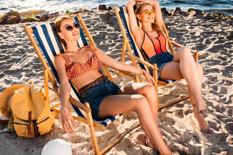 belles jeunes femmes se reposant sur des chaises longues image libre de droits