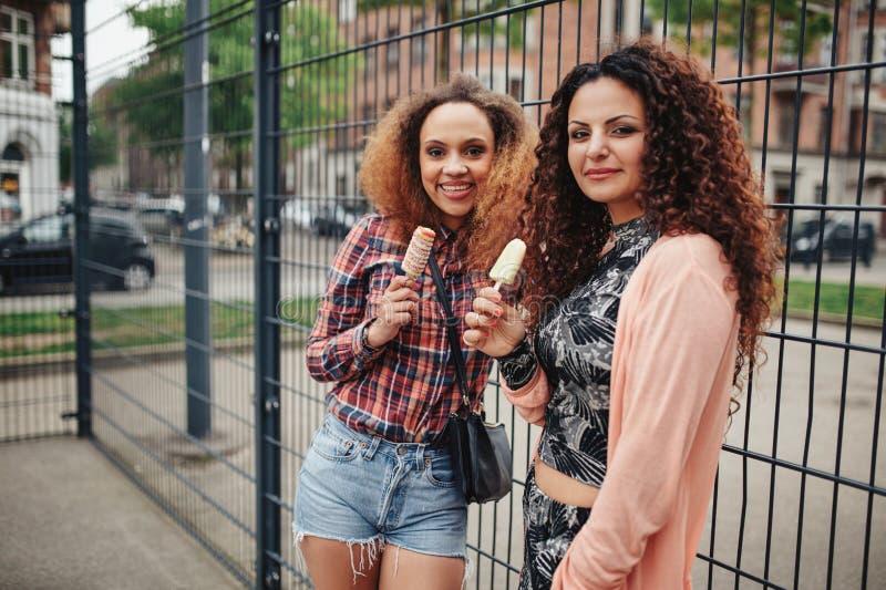 Belles jeunes filles mangeant la crème glacée  photo stock