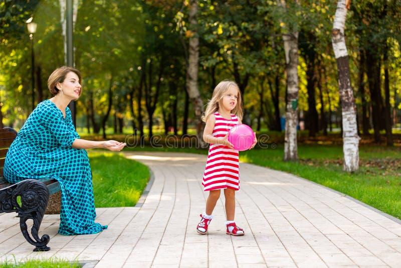 Belles jeunes maman et fille dans le jour d'été ensoleillé chaud La mère heureuse de famille et fille d'enfant la petite jouent a images libres de droits